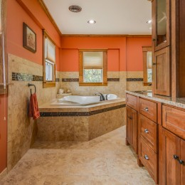 The MTI corner tub enclosed in the tile to coordinate with the bathroom. Custom shelf was designed to work with this installation. Woodpro cabinetry with a tower storage component on the countertop.