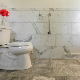Bathroom with 12x24 wainscot marble tile. Grab bar for accessibility and comfort-height toilet by Wellworth.