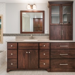 Woodpro cabinetry with a countertop storage tower.  Mitre-framed mirror.  Countertop is cultured marble with integral square bowl. Kohler Alteo 2 handled faucet.  Electrical outlet has a USB  charging capability.