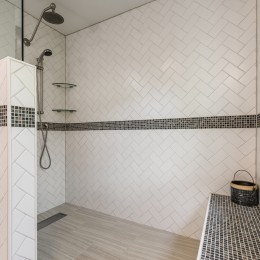 Project features a barrier-free shower with white matte subway tile in a herringbone pattern. Brushed nickel trench drain with a glass panel for water containment. Zoe rain head shower with a handheld head on sidebar.  Schluter-system waterproofing.  The bench is a custom design/build and the corner shelves are removable.
